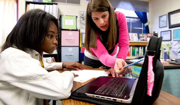 Student Aklya Thomas and teacher Faren Fransworth use a digital textbook to during a math class at Burney Harris Lyons Middle School in Athens, Georgia.