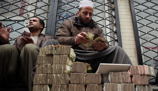 A man counts money at a Kabul market in Afghanistan.