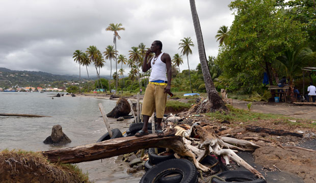 Fisherman Desmond Augustin stands on a breakwater of old tires and driftwood that local residents fashioned to try and protect their fishing village in Telegraph, Grenada.