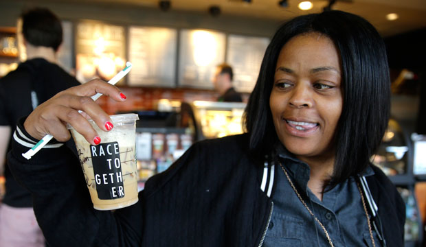 """Larenda Myres holds an iced coffee drink with a """"Race Together"""" sticker on it at a Starbucks store in Seattle on Wednesday, March 18."""