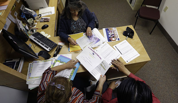 Case manager Rosario Mezo, top, helps immigrants with documents pertaining to their U.S.-born daughter at the immigration and legal services of Catholic Charities in Dallas, November 20, 2014.