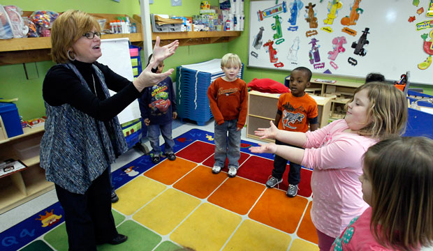West Amory Elementary School teacher Mary Sanderson, left, and her pre-K students play a color game with a orange beanbag in Amory, Mississippi.