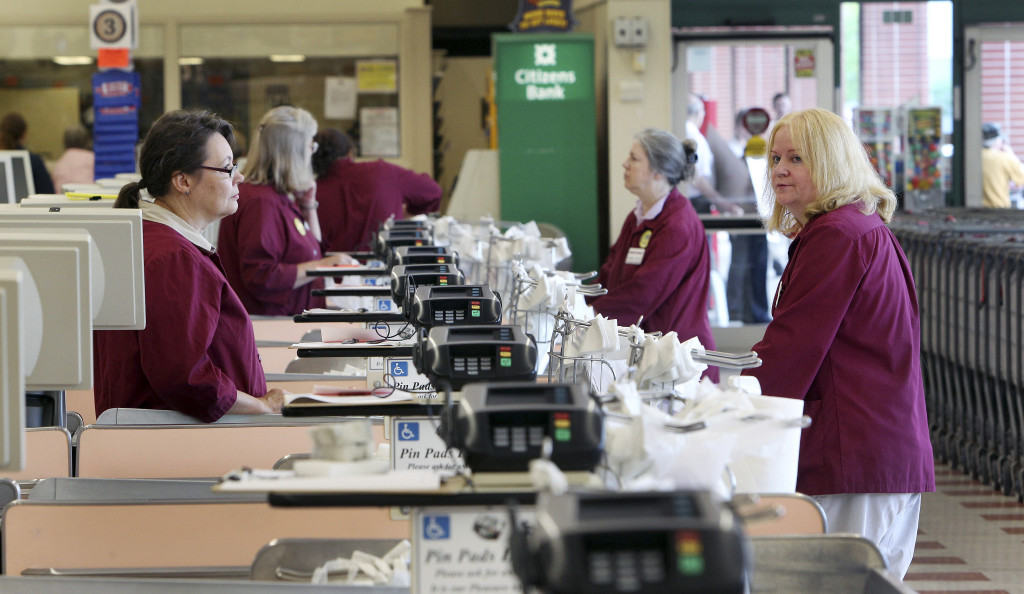 Cashiers and baggers stand idle Thursday, July 24, 2014 at a Market Basket supermarket in Concord, New Hampshire.