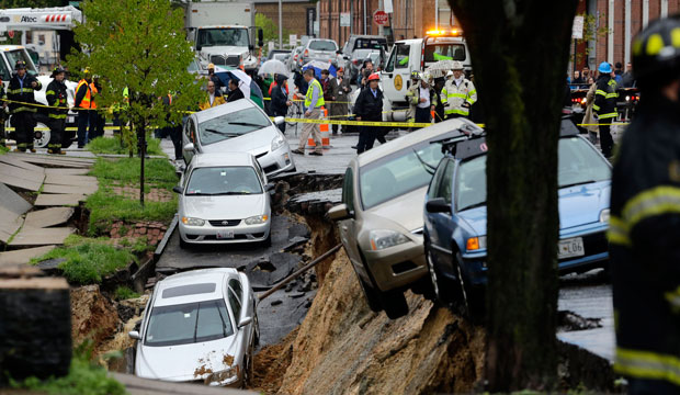 Cars sit on the edge of a sinkhole in the Charles Village neighborhood of Baltimore, April 30, 2014, as heavy rain moved through the region.