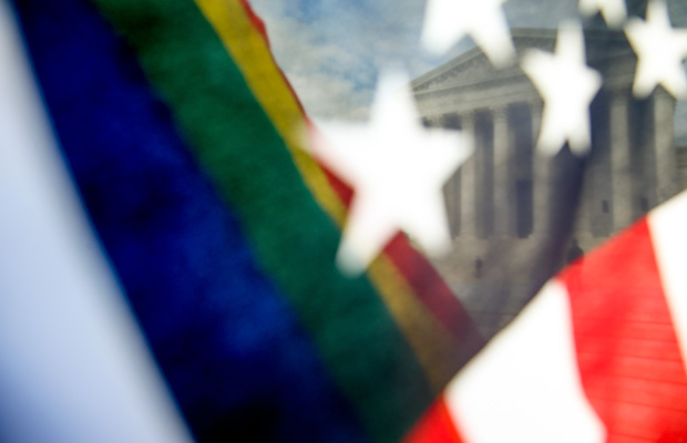 A rainbow colored flag, seen through an American flag, flies in front of the Supreme Court in Washington.