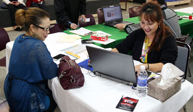 Hmong American Partnership navigator Mai Lo Lee, right, enrolls a woman in Minnesota's health insurance exchange on February 13, 2015.