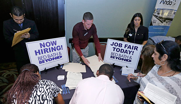 Job seekers fill out job applications at a Bed Bath & Beyond table at a job fair in Miami Lakes, Florida, October 2014.
