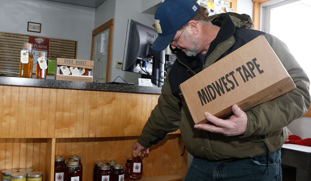 Wayne Wilkin, owner of Wilkin's Backyard Bees, restocks honey at Bucley Bros. Inc. in Wilmington, Ohio.