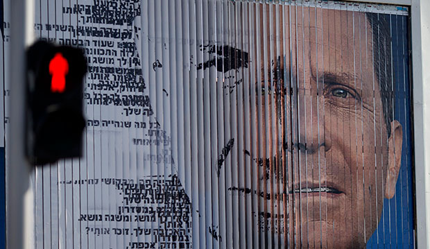 An election campaign billboard shifts between images of Isaac Herzog, leader of the Labor Party, right, and Israel's Prime Minister Benjamin Netanyahu, leader of the Likud Party, in Tel Aviv, Israel, March 5, 2015.