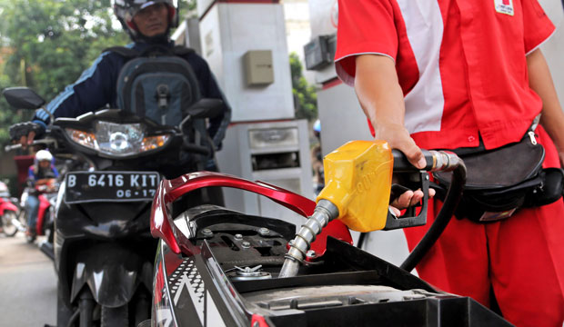An attendant fills up the tank of a motorbike at a gas station in Jakarta, Indonesia, in September 2014.