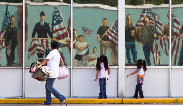 A Hispanic family walks past a reflection of a patriotic mural in Fremont, Nebraska, on July 21, 2010.
