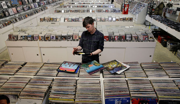 Store employee Josh Kelly checks the condition of used records at Vintage Vinyl Records on April 14, 2015.