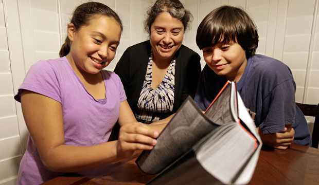 Rosaisela Rodriguez, center, reads with her children Isabel Gutierrez, left, and Rafael Gutierrez, at their home in Pleasant Hill, California on November 10, 2014.
