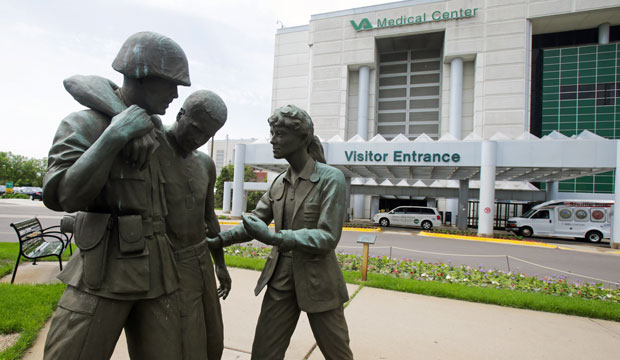 A sculpture portrays a wounded soldier being helped on the grounds of a Veterans Affairs hospital, June 9, 2014.