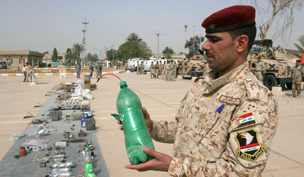 An Iraqi soldier carries a beverage bottle used as an IED that was seized by Iraqi security forces in Baghdad's Abu Ghraib suburb in 2010.