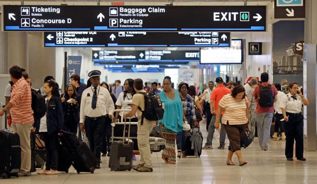 Travelers walk down the halls at Miami International Airport in Miami on Friday, May 22, 2015.