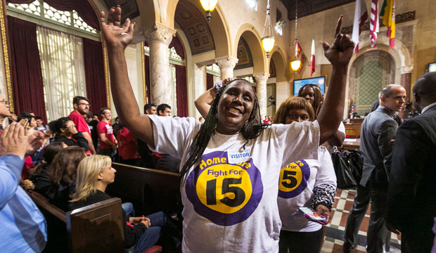 Workers react as the Los Angeles City Council, in a preliminary vote, approves a measure to raise the minimum wage to $15 an hour by 2020, June 2015.