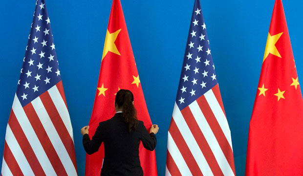 A Chinese woman adjusts the Chinese and American flags before a U.S.-China Strategic and Economic Dialogue meeting in Beijing on July 10, 2014.