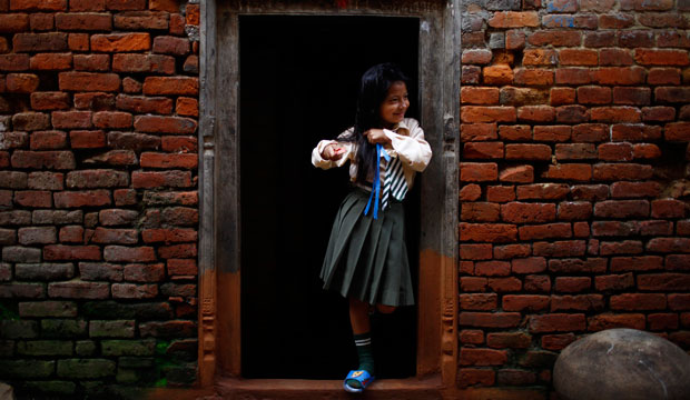 A Nepalese girl gets ready for school as she stands on the entrance to her house in Khokana, on the outskirts of Katmandu, Nepal, in August 2012.