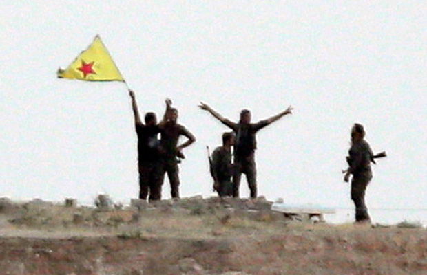 Kurdish fighters from the Kurdish People's Protection Units wave their yellow triangular flag in the outskirts of Tal Abyad, Syria.