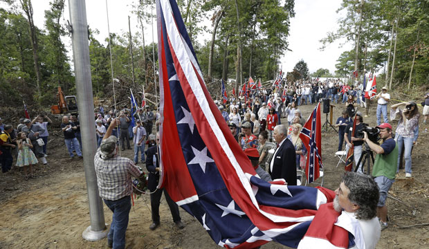 "A group called ""Virginia Flaggers"" raise the Confederate battle flag on a pole near Interstate 95 in Chester, Virginia, on September 28, 2013."