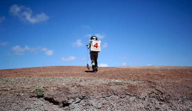A geologist hikes up a hill near the Mars Desert Research Station in Hanksville, Utah, April 19, 2015.