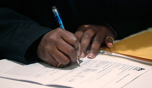 A job seeker fills out an application during a job fair in Chicago, April 22, 2015.
