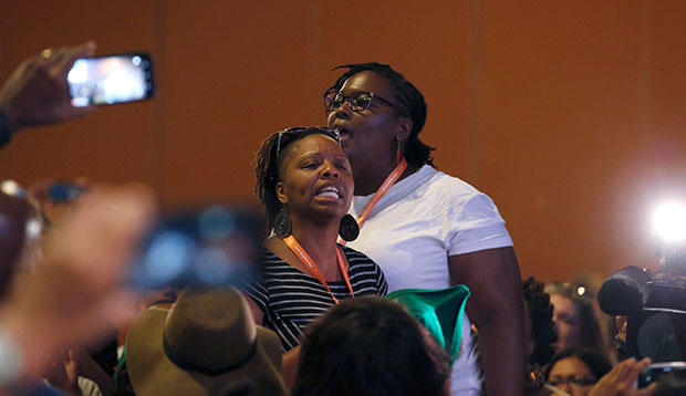 #BlackLivesMatter and Black Immigration Network activists shout down the first of two Democratic presidential candidates at a Netroots Nation town hall meeting, July 18, 2015, in Phoenix.