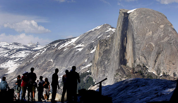 Visitors view Half Dome from Glacier Point at Yosemite National Park, California.