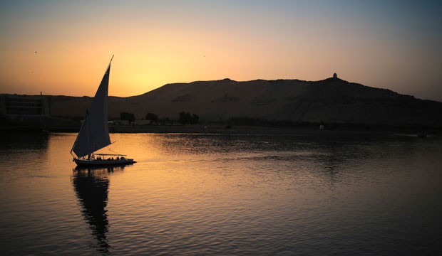 A boat carrying tourists and locals sails in the Nile River at sunset in Aswan, Egypt, April 2015.