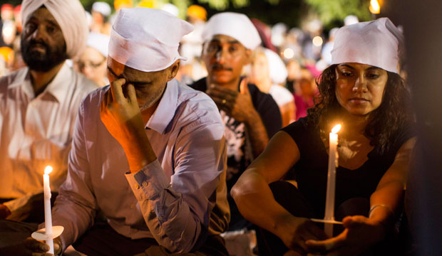 People attend a candlelight vigil for the victims of the mass shooting at the Sikh Temple of Wisconsin in Oak Creek.