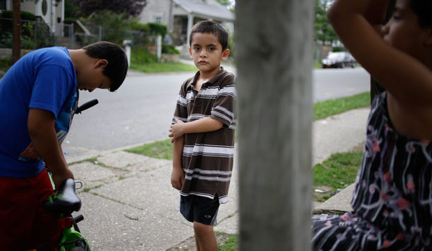 Kevin Torres, age 7, who arrived in the United States unaccompanied from El Salvador, plays with neighbors outside his apartment building in Huntington Station, New York, in 2014.