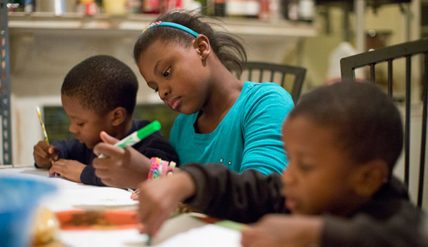 A girl helps her brothers with a drawing and homework in Philadelphia, October 8, 2013.