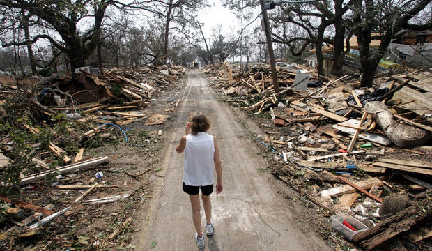 Rhonda Braden walks through the destruction brought by Hurricane Katrina in her childhood neighborhood on August 31, 2005, in Long Beach, Mississippi.