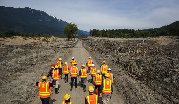 Officials walk into the debris field as Washington State Gov. Jay Inslee checks on progress at the site of the Oso mudslide on May 15, 2014 in Oso, Washington.