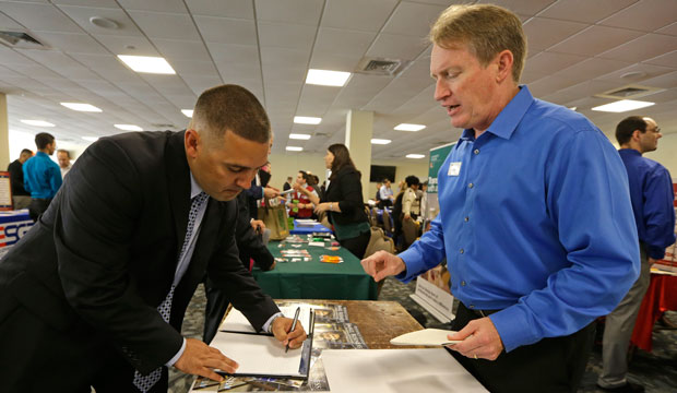 Ignacio Yanes writes information given by Jim Brooks of the Small Business Administration at the annual Veterans Career and Resource Fair in Miami, Florida, February 2015.