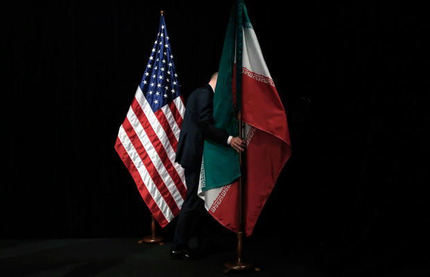 A staff member removes flags from the stage during the Iran nuclear talks in Vienna, Austria, July 14, 2015.