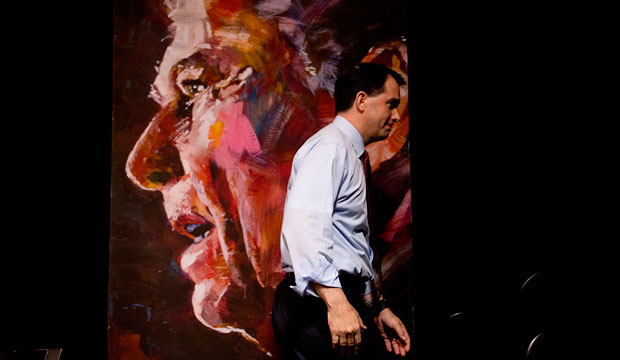 Wisconsin Gov. Scott Walker walks past a portrait of former President Ronald Reagan as he leaves the stage after speaking  in Atlanta on August 8, 2015.