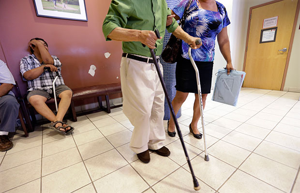 A man using two canes is helped in the waiting area at Nuestra Clinica Del Valle in San Juan, Texas.