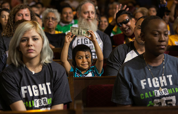 A child, center, with his father, right, raises a dollar bill as workers await the Los Angeles City Council's vote to raise the city's minimum wage to $15 per hour by 2020, June 3, 2015.
