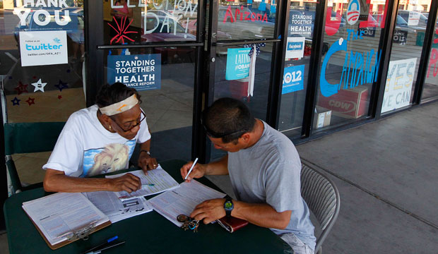Campaign volunteer Vergie Morris, left, registers Valentin Navarro to vote on June 29, 2012, in Phoenix.
