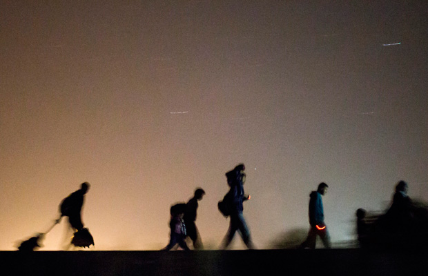 Migrants walk toward a checkpoint along the railway tracks near the border between Hungary and Serbia on September 13, 2015.