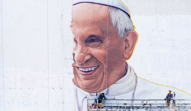 Painters work on a mural of Pope Francis on the side of a New York City building on August 28, 2015.