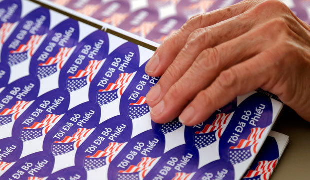 """A poll worker moves Vietnamese """"I voted"""" stickers during elections, November 2014."""