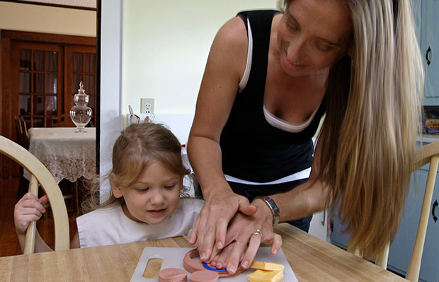 Lilly Hovis, 3, gets some help from her mother, Michelle, as they cut lunch meat into shapes for a picnic at their home in Iron Station, North Carolina, June 2008.