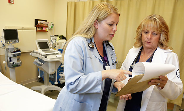Nurse practitioners go over a patient's chart at Ingalls Family Care Center in Flossmoor, Illinois, June 2013.