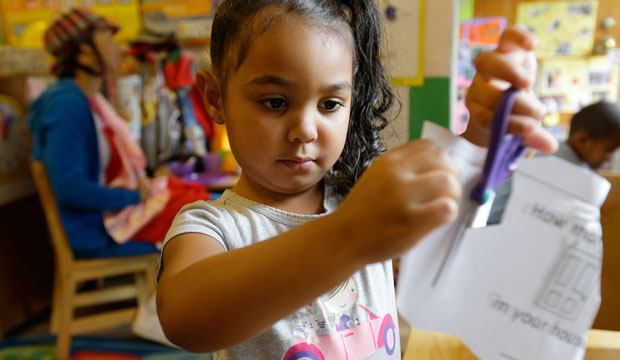 Isis Morton works with scissors and paper in a pre-kindergarten class at the Community Day Center for Children in Seattle, Washington, on October 21, 2014.