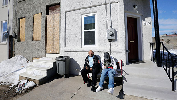 Family members sit in front of their refurbished home in Camden, New Jersey, February 23, 2015.