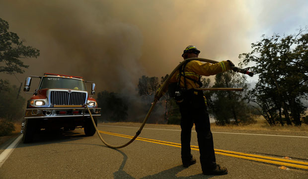 A firefighter watches a fire burn along Morgan Valley Road near Lower Lake, California, on August 13, 2015.