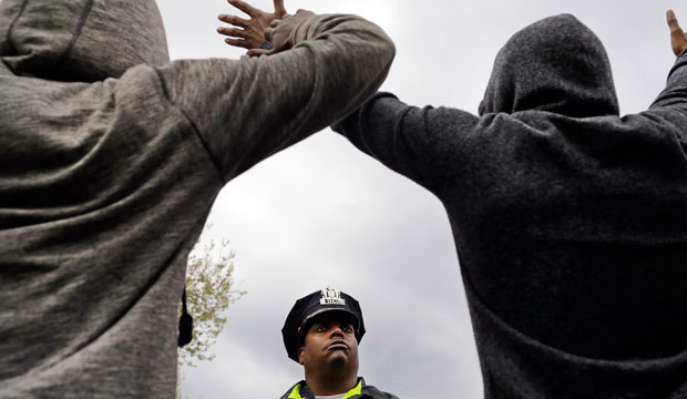 A Baltimore police officer stands guard outside of the Western District police station as men hold their hands up in protest during a march for Freddie Gray on April 22, 2015.